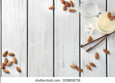 Jar with tasty vanilla pudding and almond on wooden background