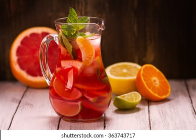 Jar of traditional red spanish sangria drink with different citrus fruits and mint over grunge wooden background. Selective focus