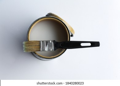 A jar of varnish for covering wooden objects and a paintbrush on a white background. View from above.