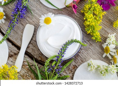 Jar with white face cream (moisturizer, mask, ointment). Natural skin care concept. Old wooden background with wild flowers. Top view, copy space.