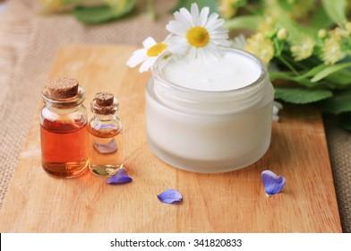 jar of white freshly made skin cream, essential oils bottles, fresh herbs and flowers. Domestic garden ingredients healthy cosmetics
