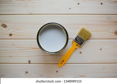 A jar of white paint next to a brush on a wooden background. Top view.  Renovation concept.