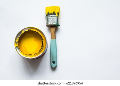 jar with a yellow paint, on it is a brush, a white background, a place for a signature