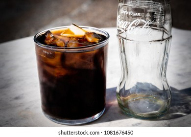 JARFALLA, SWEDEN - APRIL 16, 2018: Close-up image of a empty Coca-Cola bottle and a glass with ice and drink on a table outdoors in Jarfalla Sweden April 16, 2018.