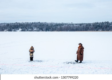 JARFALLA, SWEDEN - JANUARY 27, 2019: Winter landscape view of a man and child on a frozen lake ice fishing in Jarfalla Sweden January 27, 2019.