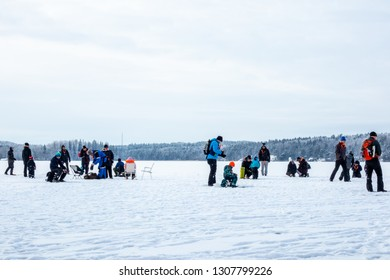 JARFALLA, SWEDEN - JANUARY 27, 2019: Low angle winter landscape view of many people on a frozen lake ice fishing in Jarfalla Sweden January 27, 2019.