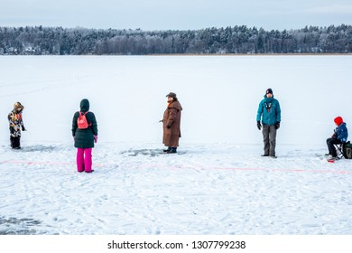 JARFALLA, SWEDEN - JANUARY 27, 2019: Winter landscape view of a small group of people on a frozen lake ice fishing in Jarfalla Sweden January 27, 2019.