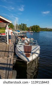 JARFALLA, SWEDEN - JUNE 9, 2018: Vertical seascape front view of people on a moored motorboat at a boat refueling station with sailboats, water and trees in the background in Jarfalla June 9, 2018.
