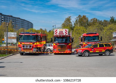 JARFALLA, SWEDEN - MAY 6, 2018: Front view of three red Swedish fire-engines and a car parked outdoors in Jarfalla May 6, 2018.