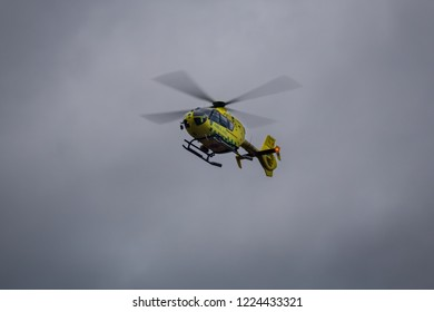JARFALLA, SWEDEN - OCTOBER 25, 2014: View from below of a yellow ambulance helicopter in mid air during bad weather with gray sky and clouds in Jarfalla Sweden October 25, 2014.