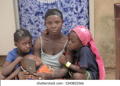 Jarra region, the Gambia, Africa: May 27, 2018: horizontal photography of a young african woman sitting, holding a smartphone, with two small kids looking at the screen, outdoors on a sunny day