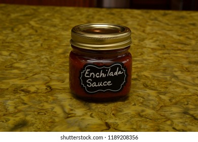 Jarred enchilada sauce on a green table cloth