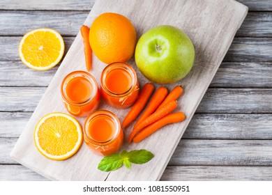 Jars with carrot juice, apple, mint leaf and sliced orange