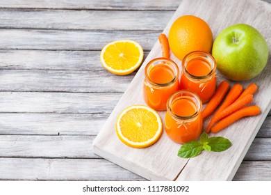 Jars with carrot juice, apple, sliced orange and mint leaf