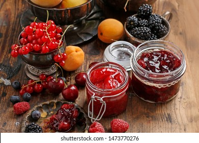 Jars of cherry strawberry jam among summer and autumn fruits on a wooden table.