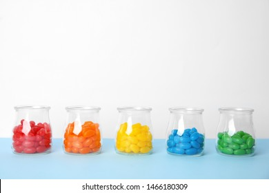 Jars of colorful jelly beans on table. Space for text