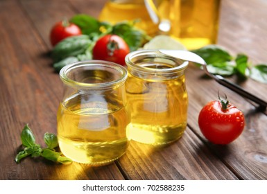 Jars with cooking oil and tomatoes on wooden table