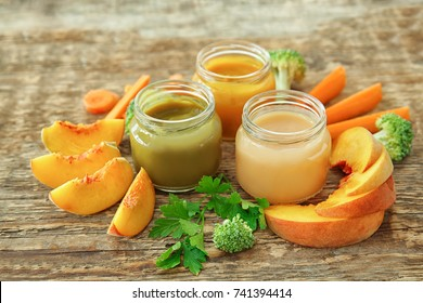 Jars with different baby food on wooden table