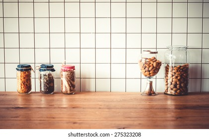 Jars with different grocery items on wooden kitchen table. Toned image