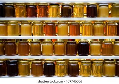 Jars of different honey varieties stocked on a shelf