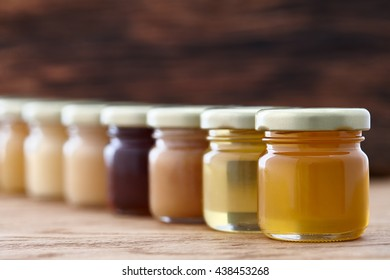 Jars with different kinds of honey in a row on a dark wooden background