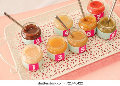 "Jars with different puree on table. Game ""Guess taste"" for baby shower party"