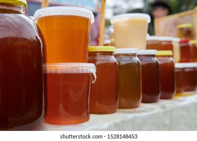 A lot of jars with different types of honey at the market. Healthy homemade product on the table. Amber, orange and brown liquids. Business of a beekeeper.