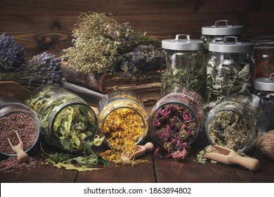 Jars of dry medicinal herbs - heather, calendula, coneflowers, linden tree flowers, melissa, bunches of dry plants, old books on wooden table. Alternative medicine.