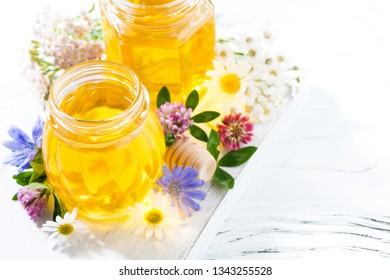 jars with flower honey on white wooden background, closeup