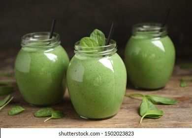 Jars of healthy green smoothie with fresh spinach on wooden table