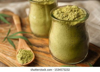 Jars of hemp protein powder on wooden board, closeup. Space for text