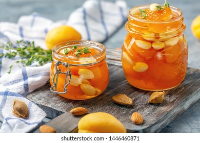 Jars of homemade apricot jam with almonds and thyme on a wooden serving board, selective focus.