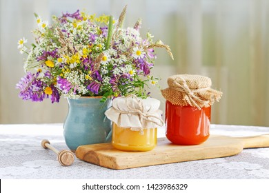 Jars with honey and bouquet of wild flowers on the table.