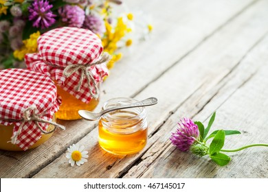 Jars of honey and healing herbs bunch on table with copy space. Herbal medicine and nutraceuticals.