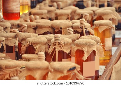 Jars and honey sticks with  natural honey on shelf in shop. Sale of natural honey in market. Production of honey.
