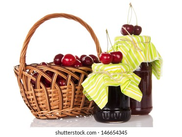 Jars of jam, a wicker basket with the sweet cherries and some berries on the jars, isolated on white