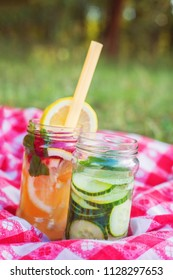 Jars of lemonade and cucumner on a sunny day on a picnic table cloth