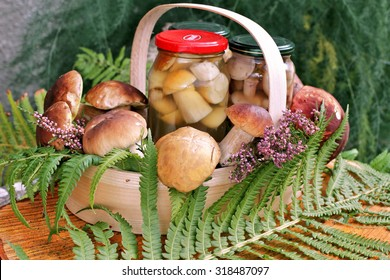 Jars  with  marinated boletus in basket   and fern