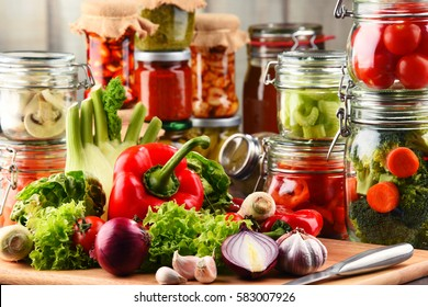 Jars with marinated food and raw vegetables on cutting board.