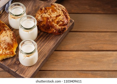 Jars with milk and bread buns on a cutting board