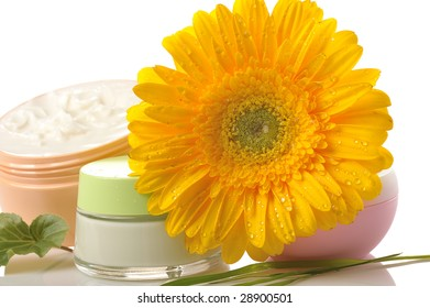 jars of natural cosmetic creams with yellow gerbera on white