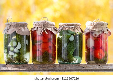 Jars of pickled vegetables: cucumbers, tomatoes on a wooden shelf. Marinated and  organic raw vegetables