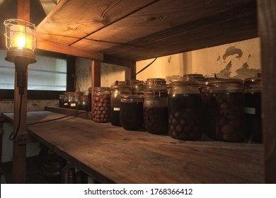 Jars with pickled vegetables, fruity compotes and jams in abandoned basement with a light hanging Preserved food in a dark cellar wooden shelf