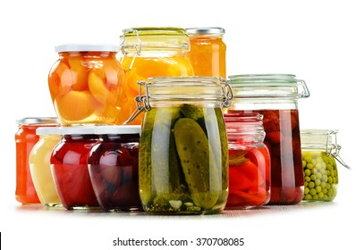 Jars with pickled vegetables, fruity compotes and jams isolated on white background. Preserved food