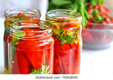 Jars of pickled vegetables: organic red pepper and green parsley. Marinated and canned food.