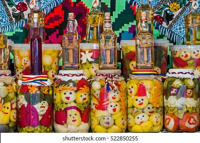 Jars with pickles and bottles with alcohol, traditional from area Maramures, Romania, displayed on a background with traditional embroidery.