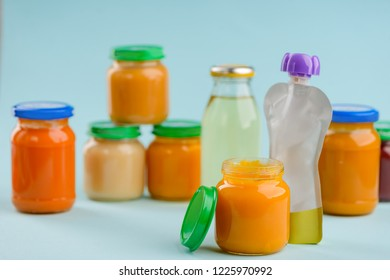 Jars and pouch of puree, bottle of juice on blue background. Mashed vegetables and fruits. Wide selection of baby food.