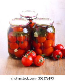 Jars with  preserved pickled tomatoes on table