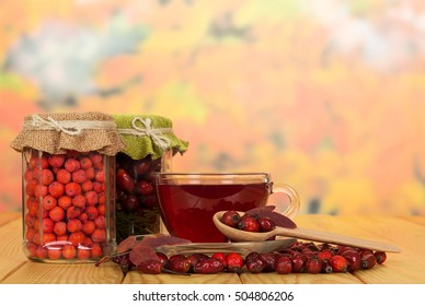 Jars with rowan berries and rose hips, a wooden spoon, a cup of tea on a background of autumn leaves.