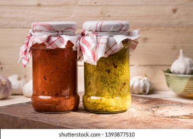 Jars of south Indian spicy green chilly pickle and garlic pickle  on a wooden rustic background